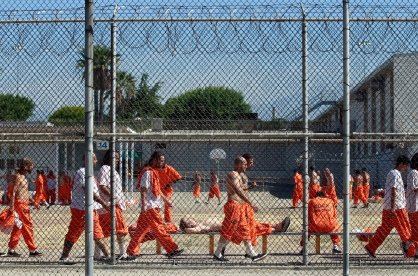 Inmates walk around an exercise yard at the California Institution for Men state prison in Chino